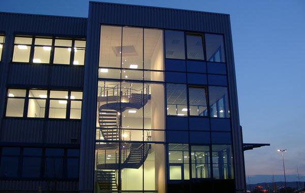 Das hell beleuchtete 3-geschossige Verwaltungsgebäude mit 2.400 m² Nutzfläche der Kardex AG bei Nacht.